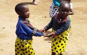 Zwei Kinder in bunter Kleidung geben sich die Hand
