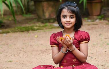 Girl holding flower in hand during Onam Festival Kerala Tour