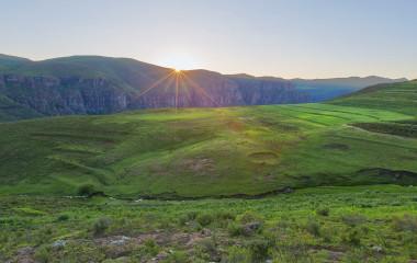 Grüne Berglandschaft mit untergehenden Sonne in Lesotho