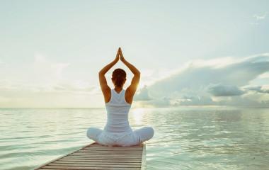 Frau praktiziert Yoga am Wasser vor dem Sonnenaufgang