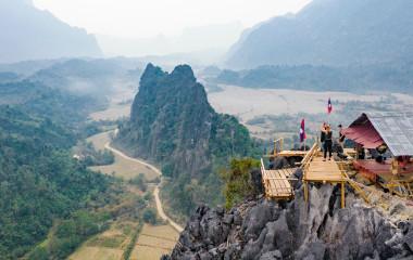 Atemberaubende Luftaufnahme einiger Touristen, die das schöne Panorama vom Aussichtspunkt Nam Xay in Vang Vieng, Laos, Asien fotografieren.