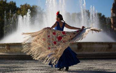 Beautiful woman dancing flamenco near the fountain
