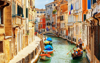 Enchanting Travels Rio Marin Canal with boats and gondolas from the Ponte de la Bergami in Venice, Italy.