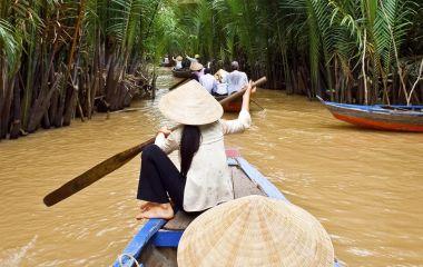 Vietnamesische Frauen steuern ein Boot durch das Mekong Delta