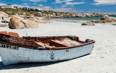 Enchanting Travels South Africa Tours Paternoster - A fishing boat on the white sand of the beach at Paternoster on a bright sunny day