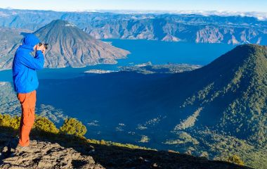 Enchanting Travels Guatemala ToursHiker with panorama view of Lake Atitlan and volcano San Pedro a