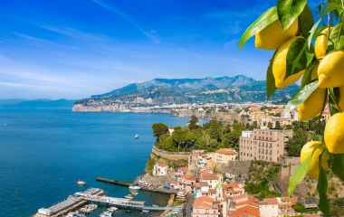 Aerial view of cliff coastline Sorrento and Gulf of Naples, Italy. Ripe yellow lemons in foreground. In Sorrento lemons are used in production of limoncello.