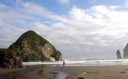 Mann spaziert am Strand mit Felsformationen in der Nähe des Hotels Tierra Chiloé, Chile