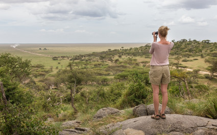 Enchanting Travels African safari parks to see - Female tourist looking through binoculars on African safari in Serengeti national park, Tanzania, Afrika.