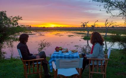 Ein Paar sitzt an einem gedeckten Tisch unter freiem Himmel und beobachtet den Sonnenuntergang in Esteros del Iberá in Argentinien