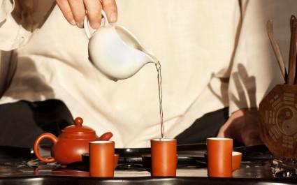 Im Rahmen einer Teezeremonie wird Tee in kleine Tassen eingeschenkt
