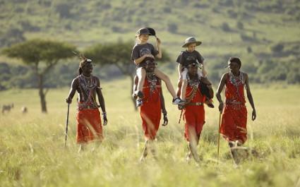 Vier Massai-Männer tragen Kinder durch die Savanne, Kenia