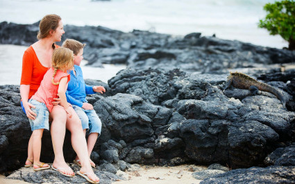Mutter und Kinder beobachten Meerechse auf den Galapagos-Inseln, Ecuador