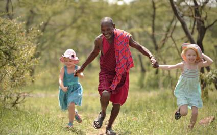 Massai in traditioneller Kleidung rennt Hand in Hand mit lachenden Kindern