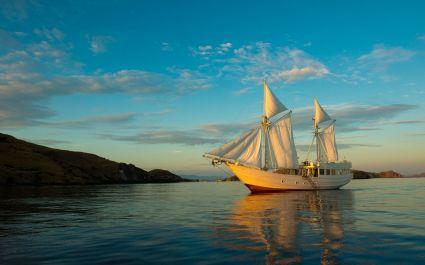Segelboot mit Segeln vor felsiger Uferlandschaft