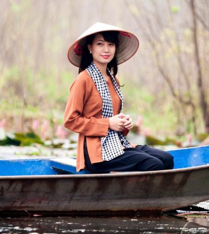 Junge Frau mit Strohhut sitzt im Kanu in Vietnam