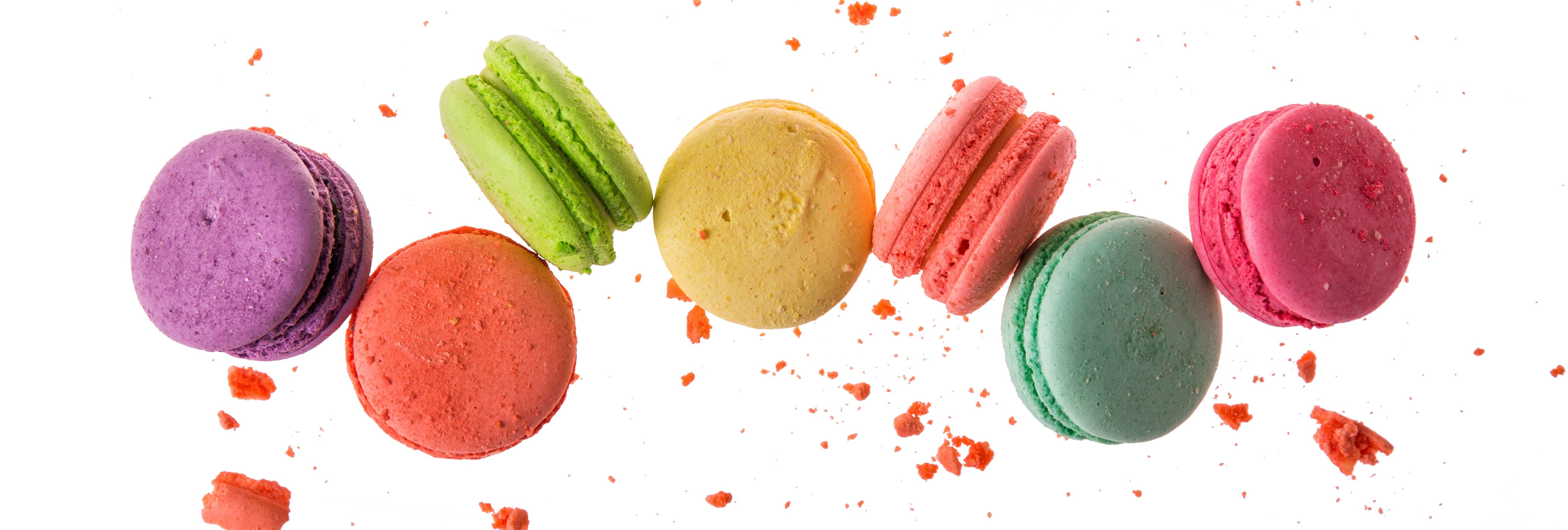 Enchanting Travels France Tours French macaroons isolated on white background. Cookies falls mixed with crumbs
