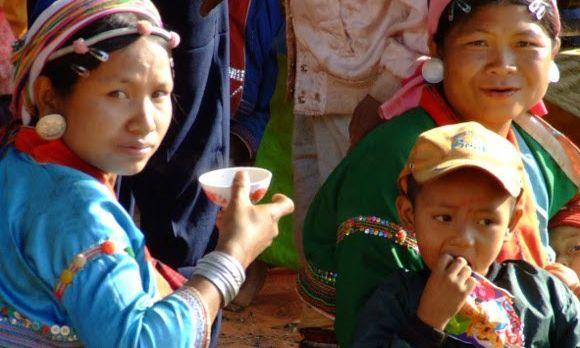 Frauen und Kinder auf einem Markt in Yangon, Myanmar, blicken in die Kamera