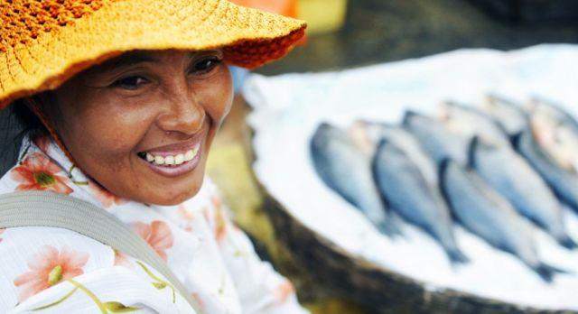 Indigenous Cambodian woman selling fish in a market, Asia, shutterstock_223792456