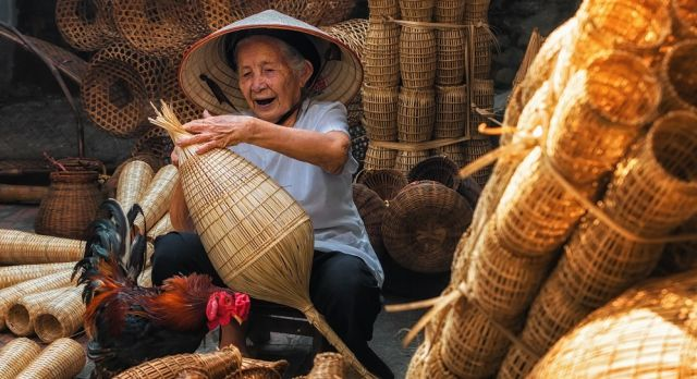 Enchanting TraOld Vietnamese female craftsman making the traditional bamboo fish trap