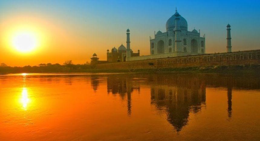 Der Taj Mahal im indischen Agra spiegelt sich im Wasser bei Sonnenuntergang