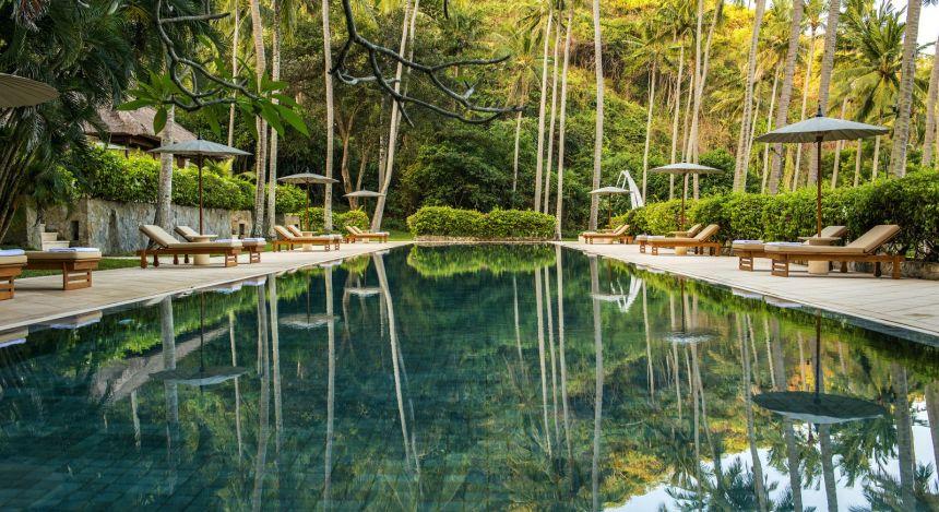 Großer Swimmingpool des Amankila inmitten tropischer Wälder