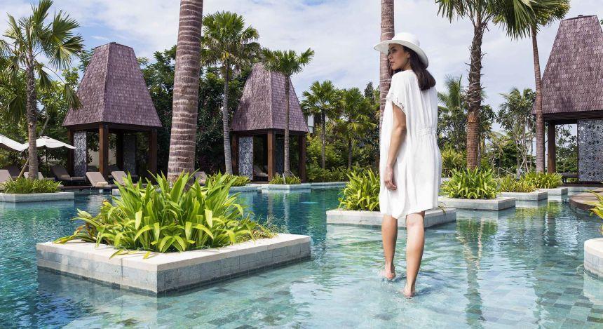 Frau geht durch das seichte Wasser des Pools im Sofitel Bali Nusa Dua Beach Resort