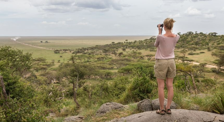 Frau überblickt mit Fernglas die Serengeti