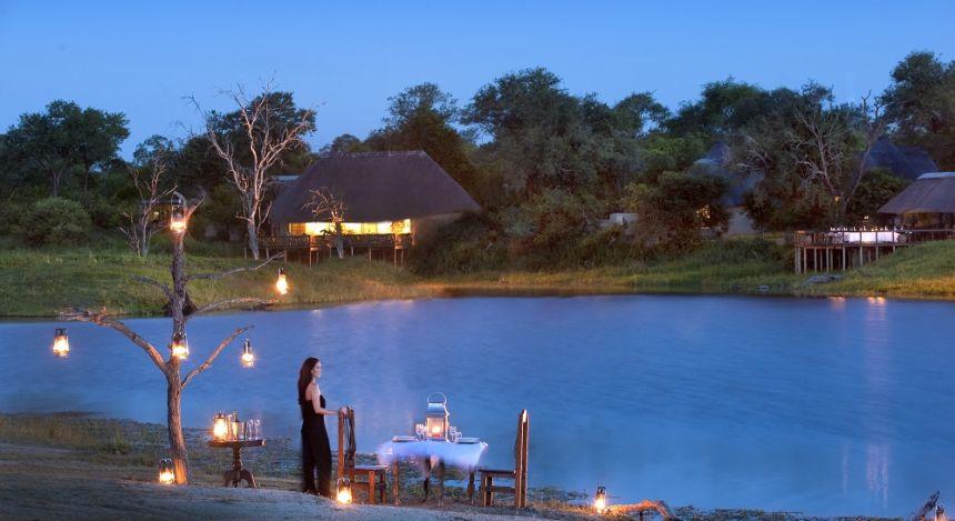 Frau steht am Ufer und gedeckten Tischen in Krüger, Südafrika