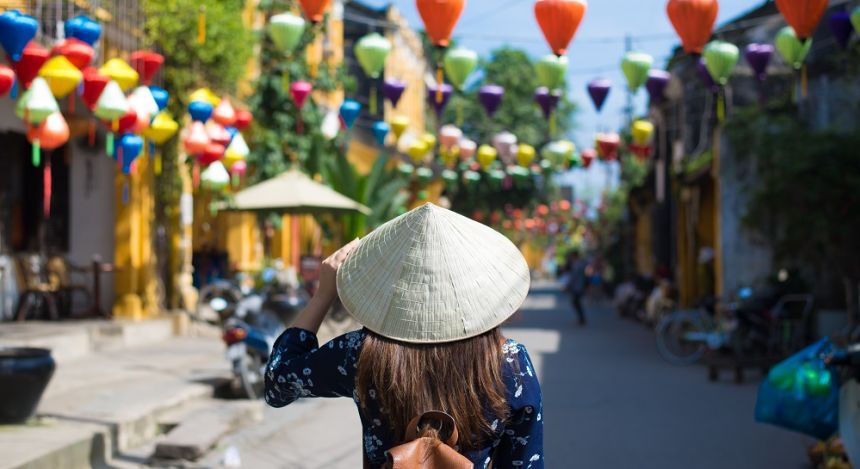 Enchanting Travels Vietnam Tours Hoi An Tourist woman is wearing Non La