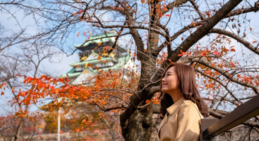 Enchanting Travels Japan Tours Osaka asian woman in the autumn garden with Osaka castle