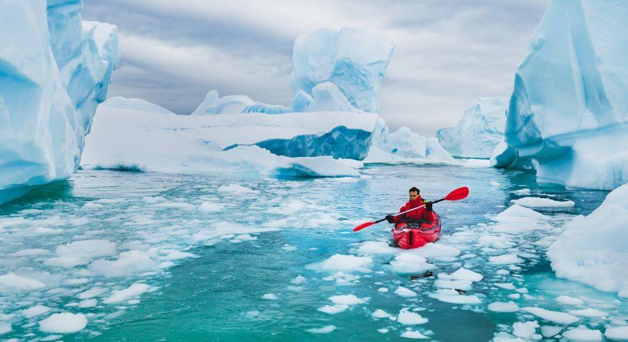 Enchanting Travels Antarctica Tours extreme tourism, winter kayaking in Antarctica, adventurous man paddling on sea kayak between icebergs