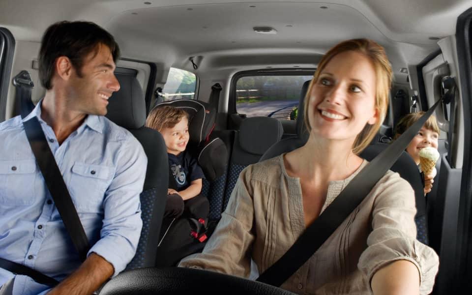 Lykkelig familie med sikkerhetseler kjører Nissan E NV 200 Evalia