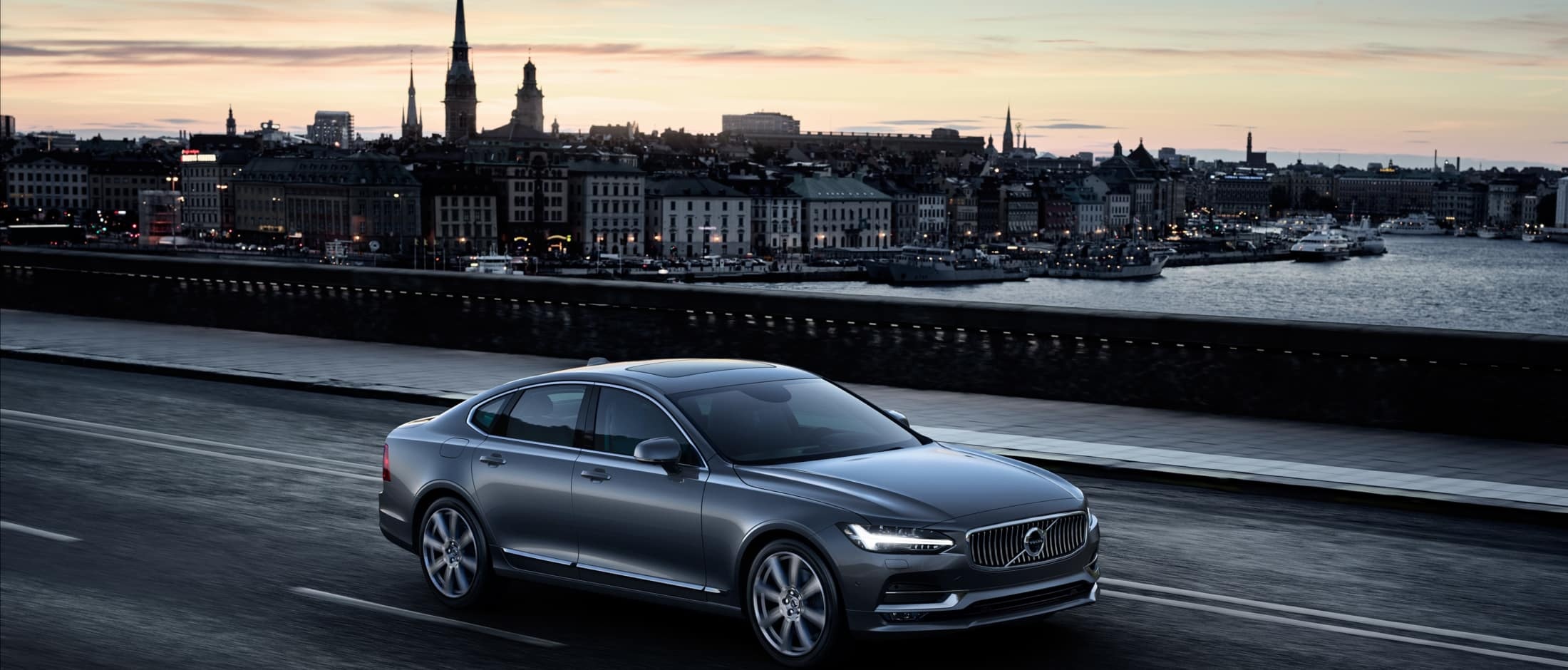 Volvo S90 Inscription i fargen Mussel Blue kjører over en bro i Stockholm