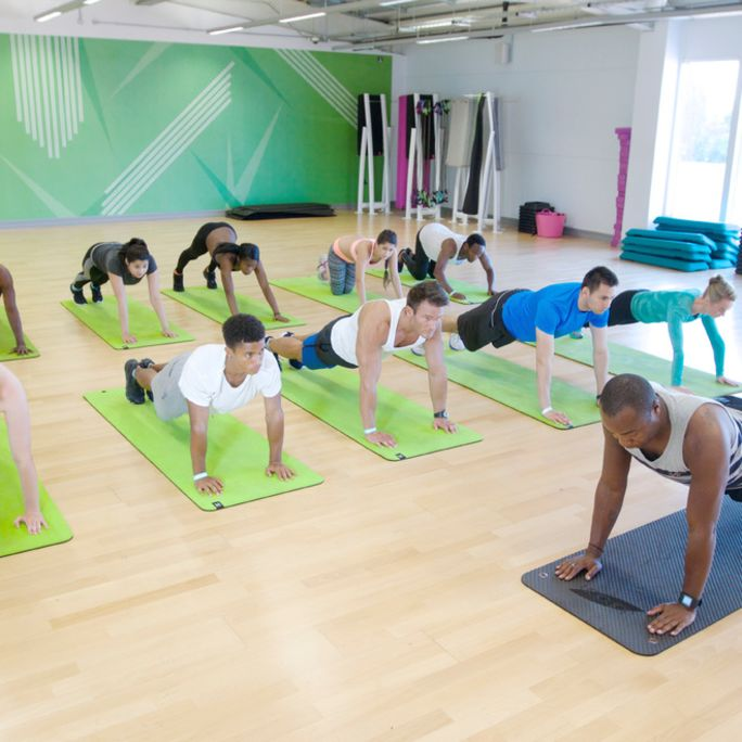 Group of people on mats doing a push up during a fitness calss