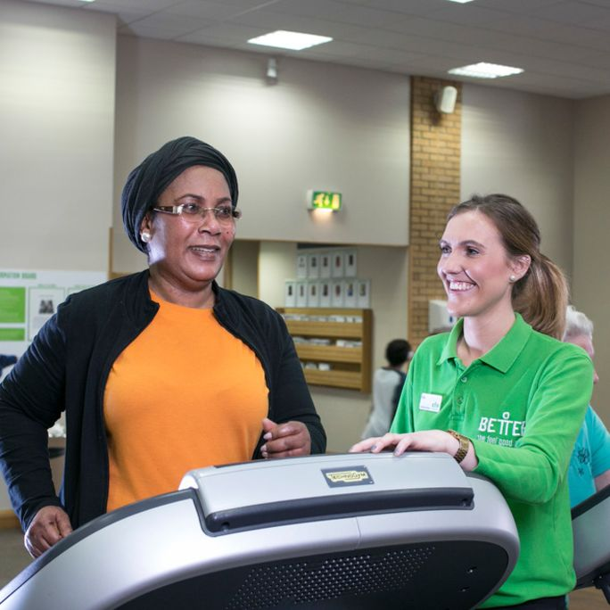 Older lady on treadmill with fitness instructor