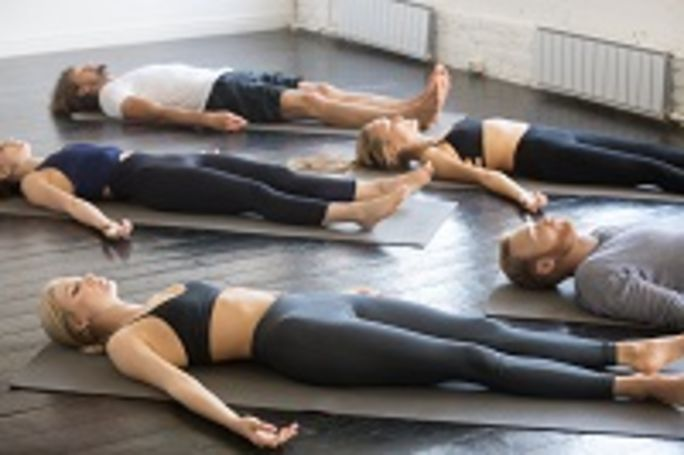 Group of people laying on the floor in a pliates class