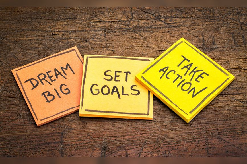 3 sticky pads, the first saying Dream Big, the second saying Set Goals, and the third saying Take Action.