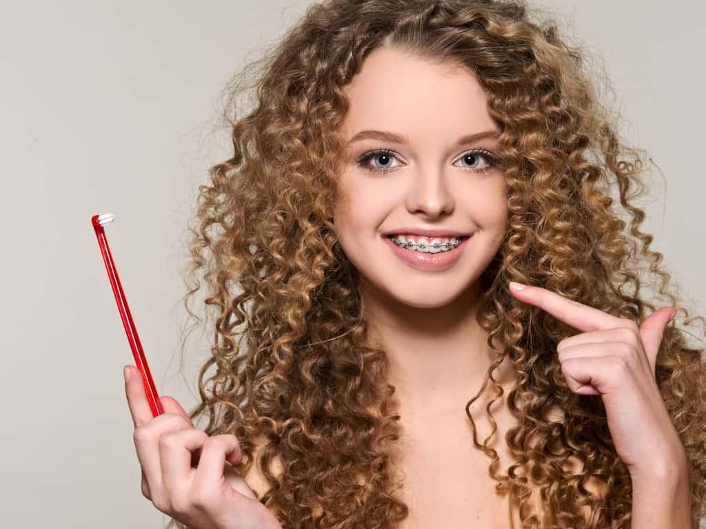 jeune fille avec bagues et brosse a dents