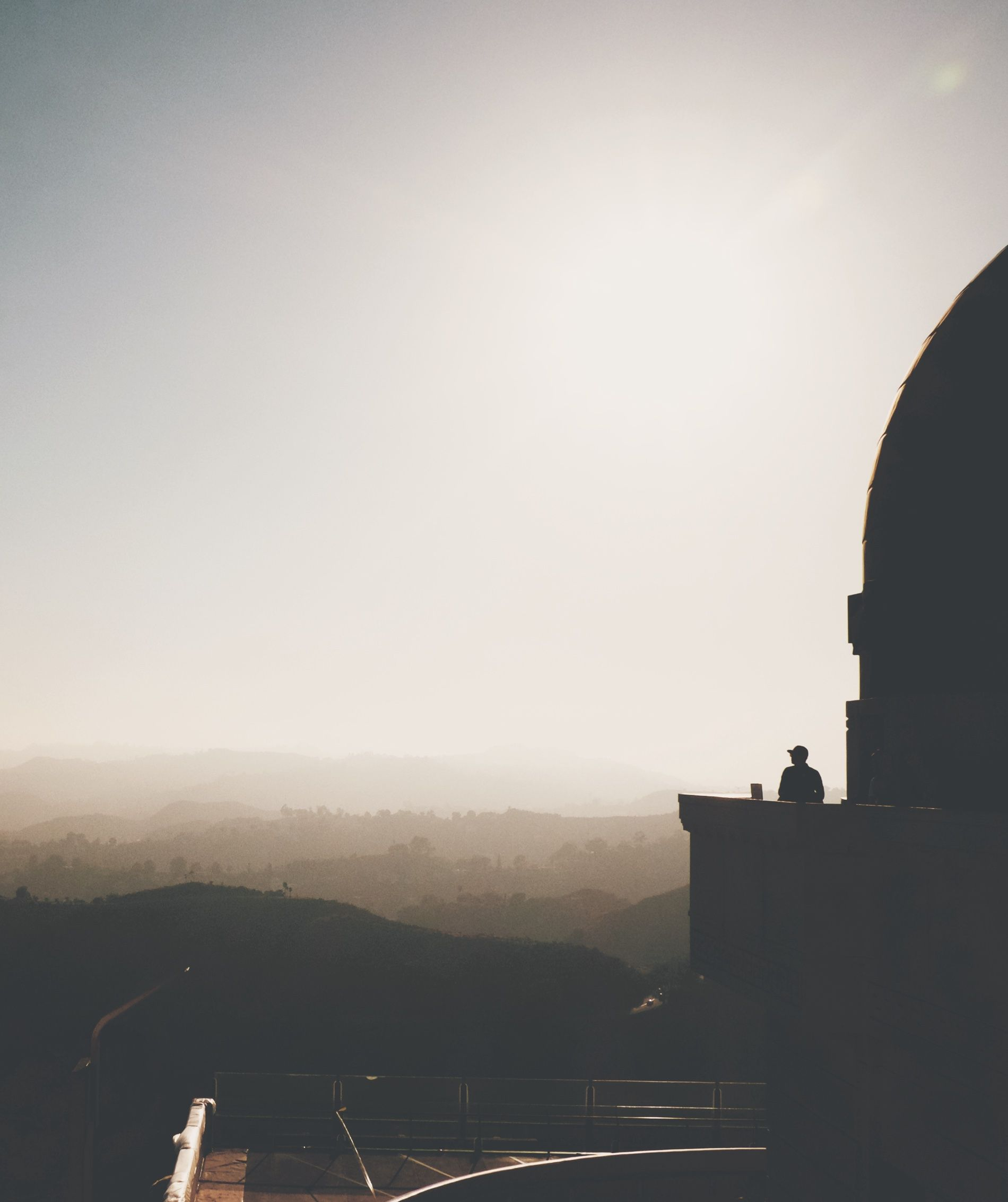Silouetted person looking out from an observatory across a hazy city with rolling hills.