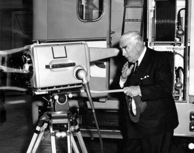 Prime Minister Robert Menzies peers into a new telecine camera for television station ADS7 at Philips Electrical Industries Factory in Adelaide, South Australia, 21 September 1959