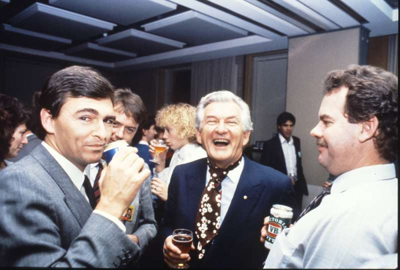 MP John Brumby (left) and Prime Minister Bob Hawke (centre) join colleagues in the Senate Committee Room for a beer and a laugh. Photographer – Robert MacFarlane, Department of the House of Representatives, MoAD Collection.