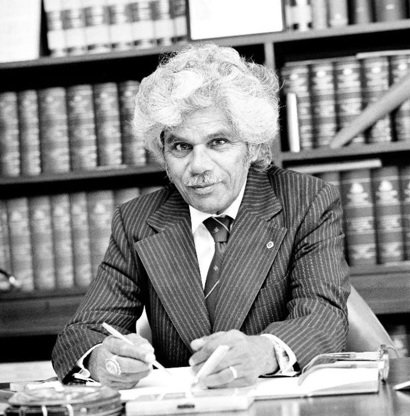 Neville Bonner in a black and white photograph, sits at a desk with a pen in hand while looking up at the camera. In the background is a bookshelf with many books. Bonner is wearing a striped suit and tie.