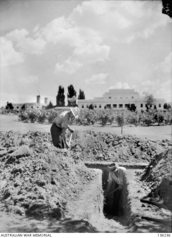 Workmen digging slit trenches in the grounds of Parliament House in preparation for air raid drills and evacuations, 1942.