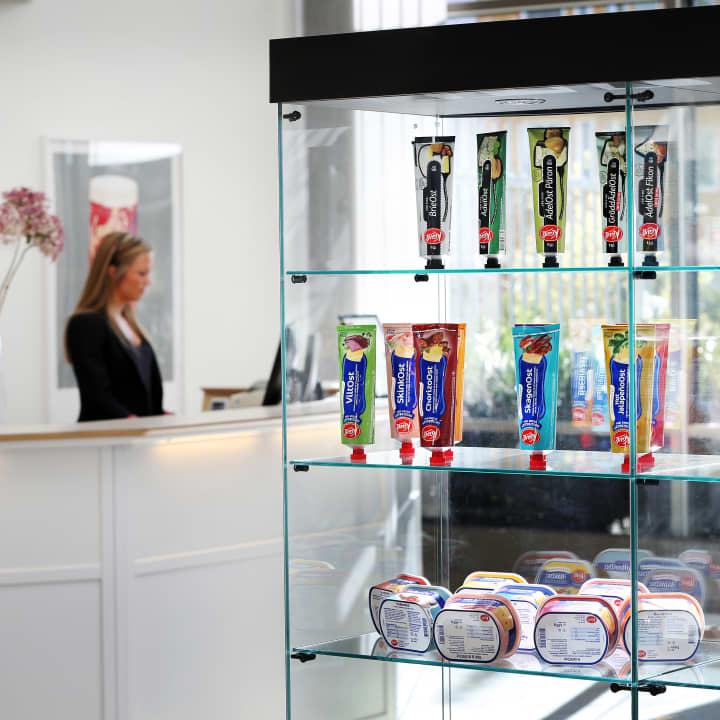 I bakgrunden står receptionist vid receptiondisk, i förgrunden ett utbud av Kavlis produkter i en glasmonter