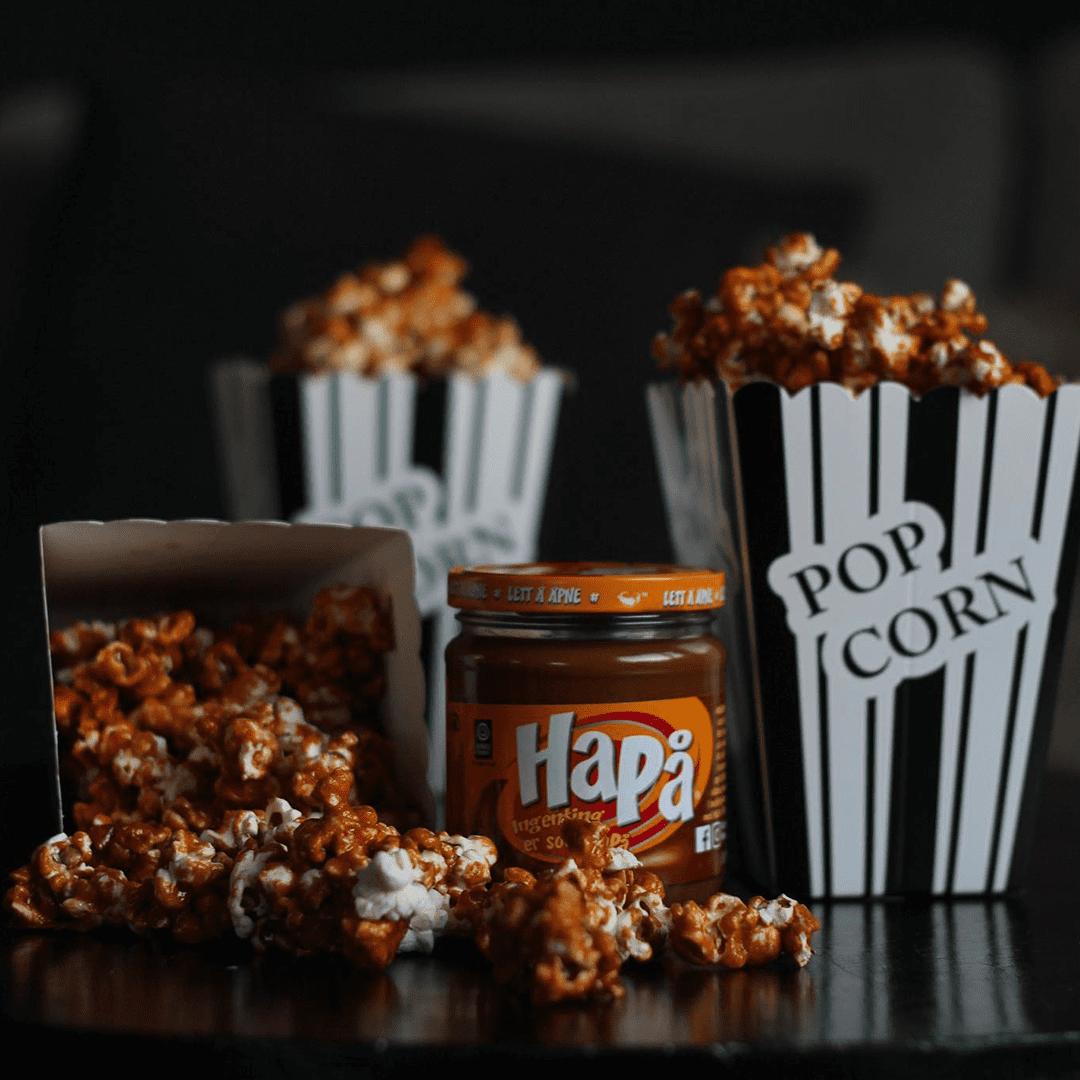 Skap kinofølelsen hjemme med klassiske popkornbegre, mobilfri sone, hjemmelagde kinobilletter eller en tavle med kinoprogrammet.