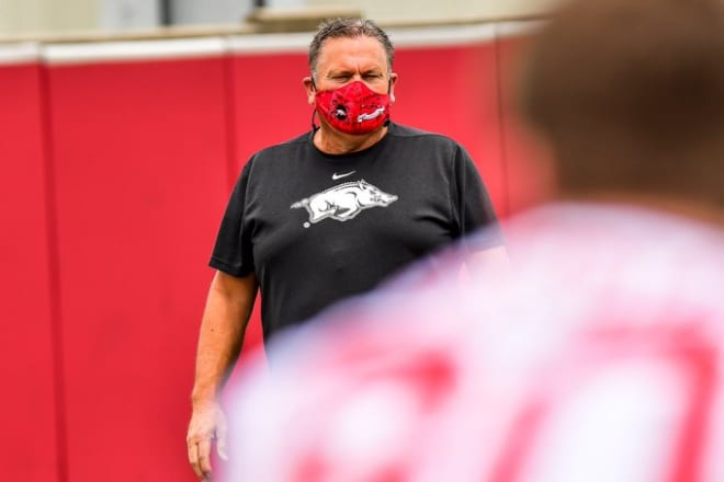Sam Pittman wears a mask as he watches his player run drills.