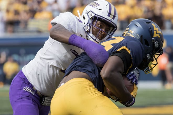 James Madison linebacker Dimitri Holloway (left) tackles West Virginia wide receiver Bryce Wheaton during the Dukes' loss earlier this season at Milan Puskar Stadium in Morgantown, W.Va.