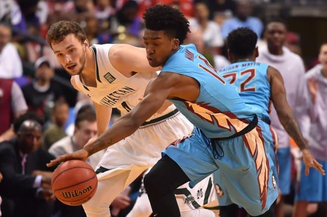 FSU sophomore Terance Mann reaches for a steal on Saturday against Manhattan.