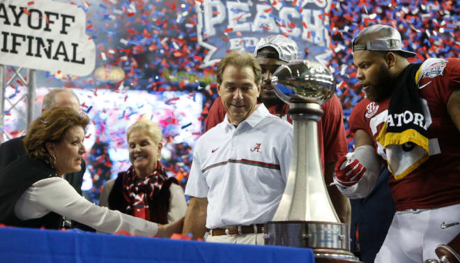 Nick Saban checks out the trophy after winning the Peach Bowl CFP semifinal.